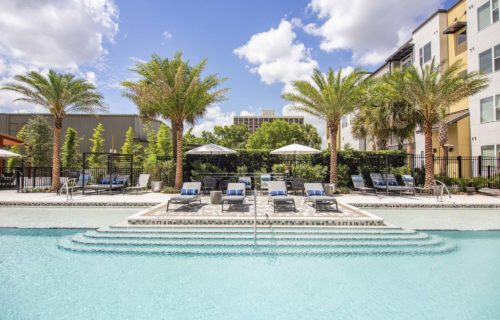Outdoor oasis with saltwater pool featuring in-water chaise loungers and shaded cabanas - Make Your Weekends Fantastic